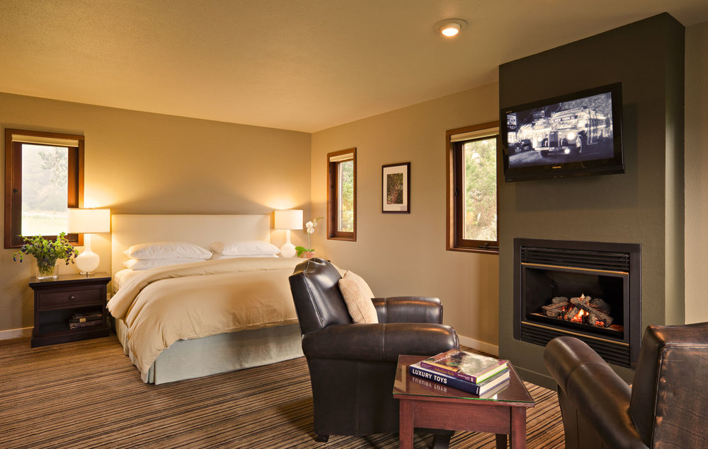 The Manzanita Room with King bed, flat screen TV, and leather armchairs around a fireplace