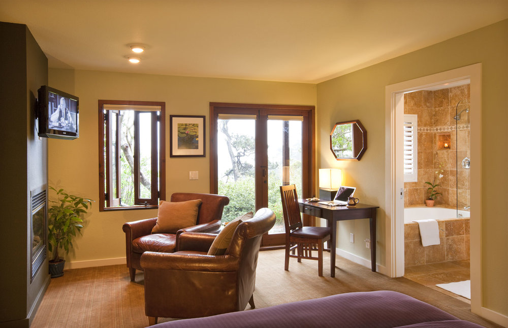The Pine room with leather chairs in front of fireplace and flat screen TV, desk, French Doors, and tiled bathroom