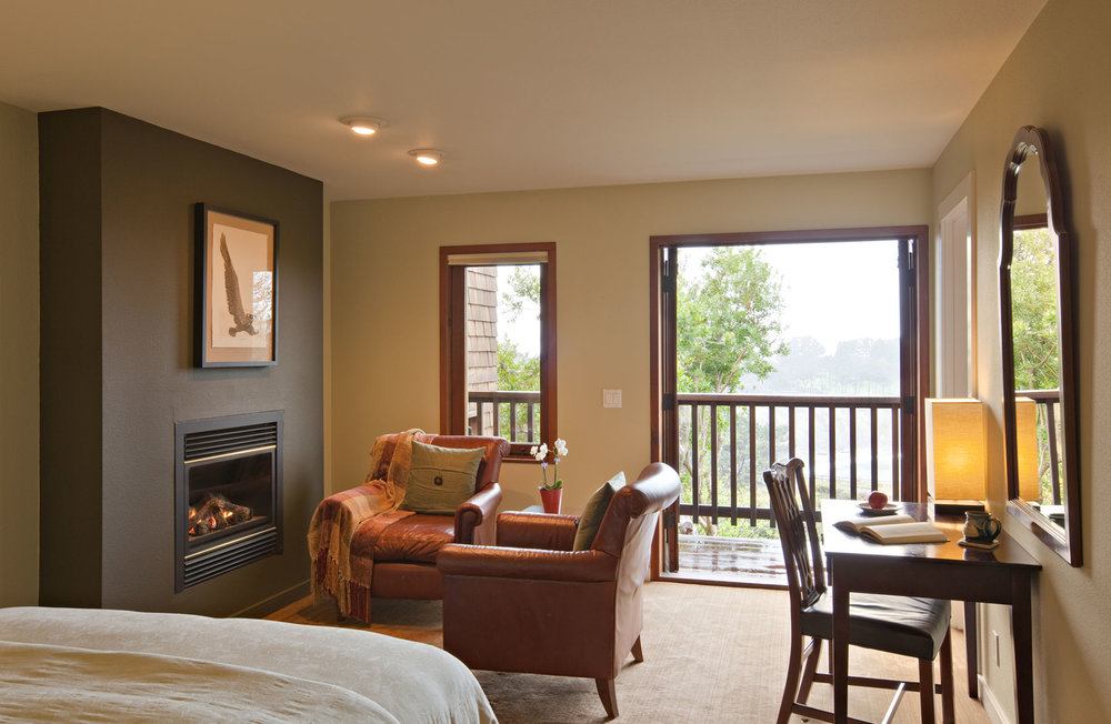 Double doors lead out onto a balcony with a view of an ocean cove beyond; a pair of leather chairs in front of a fire and a desk with chair.