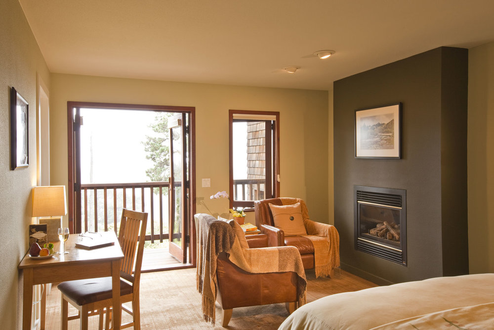 The Heron room with double doors leading out to a balcony, leather chairs next to a fireplace, and desk.