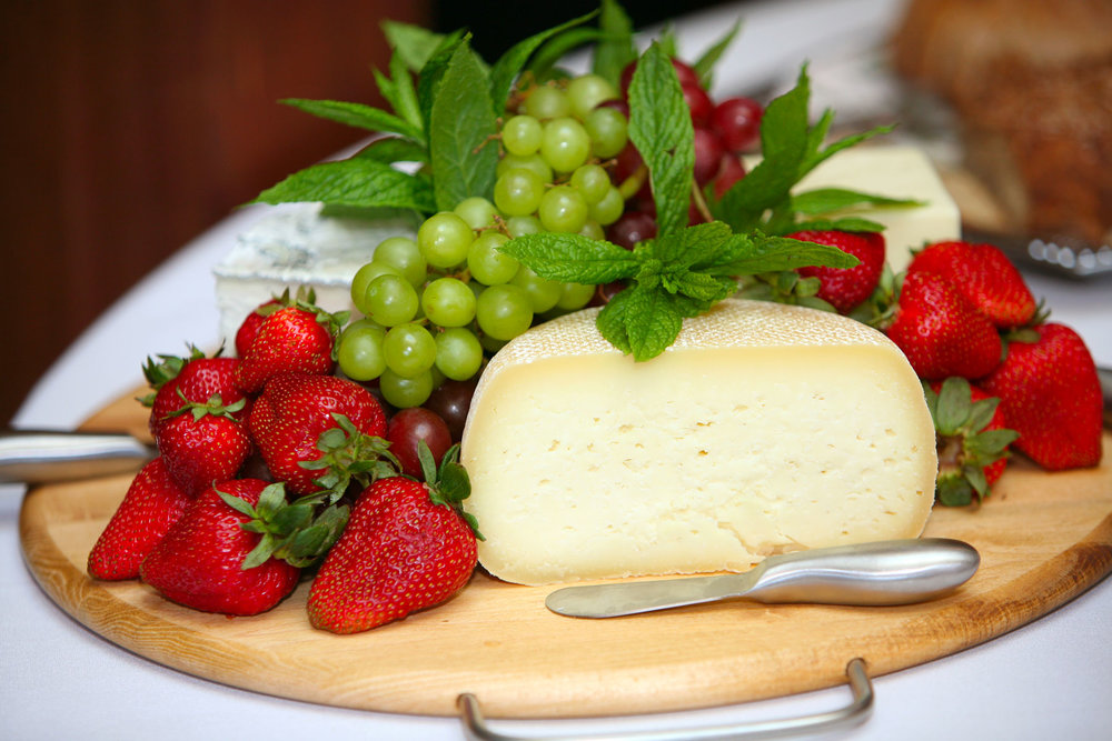 Cheese and fruit on a wooden board.