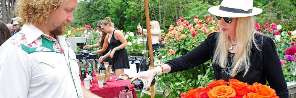 A woman pours a glass of wine for a guest at Winesong annual fundraiser event.
