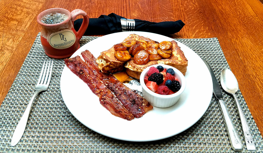 A breakfast of bananas on french toast with bacon, fruit, and coffee.