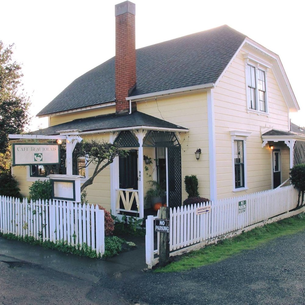 The popular Cafe Beaujoulais restaurant is housed in a quaint yellow building with white picket fence in Mendocino.