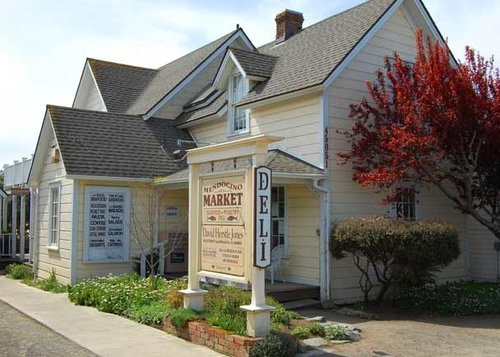 The Mendocino Market is located in a small yellow building with peaked roofs in Mendocino, California.