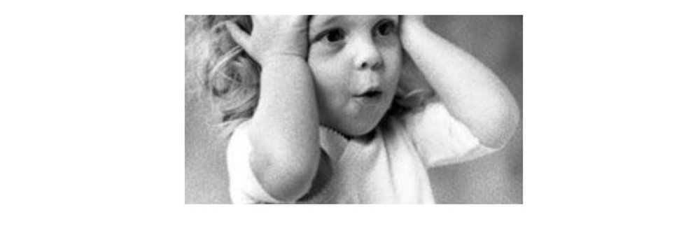 A black and white photo of a small child looking surprised with hands on either side of her head.