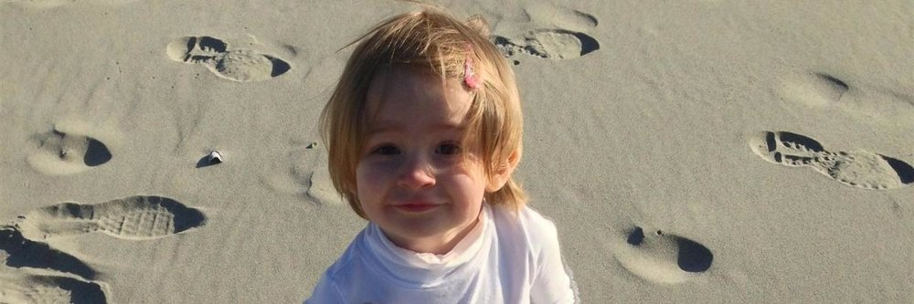 Little Ella with pink barrette in her hair looks into the camera on the beach on a sunny day