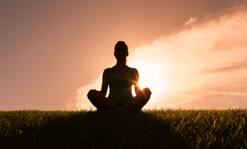 woman sitting in lotus position on a patch of grass, backlit by the sun