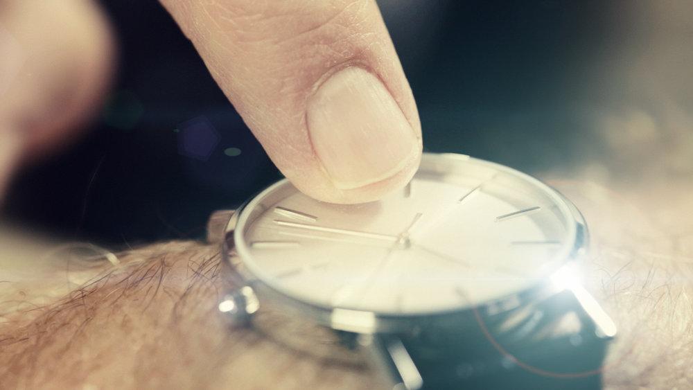 a fingertip tapping a watch face