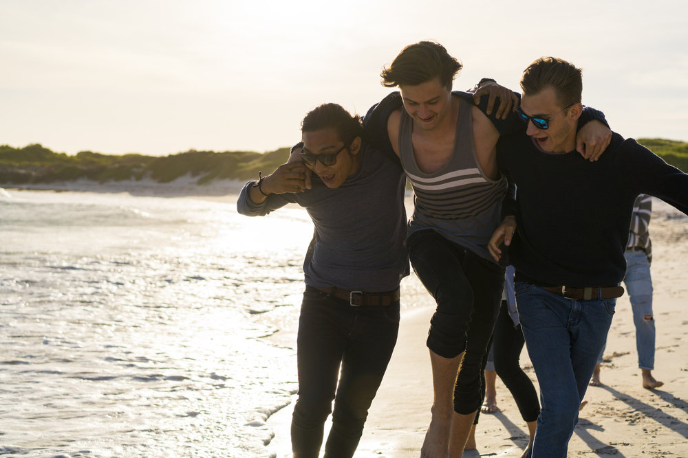 Three young men on a beach walk next to the waves