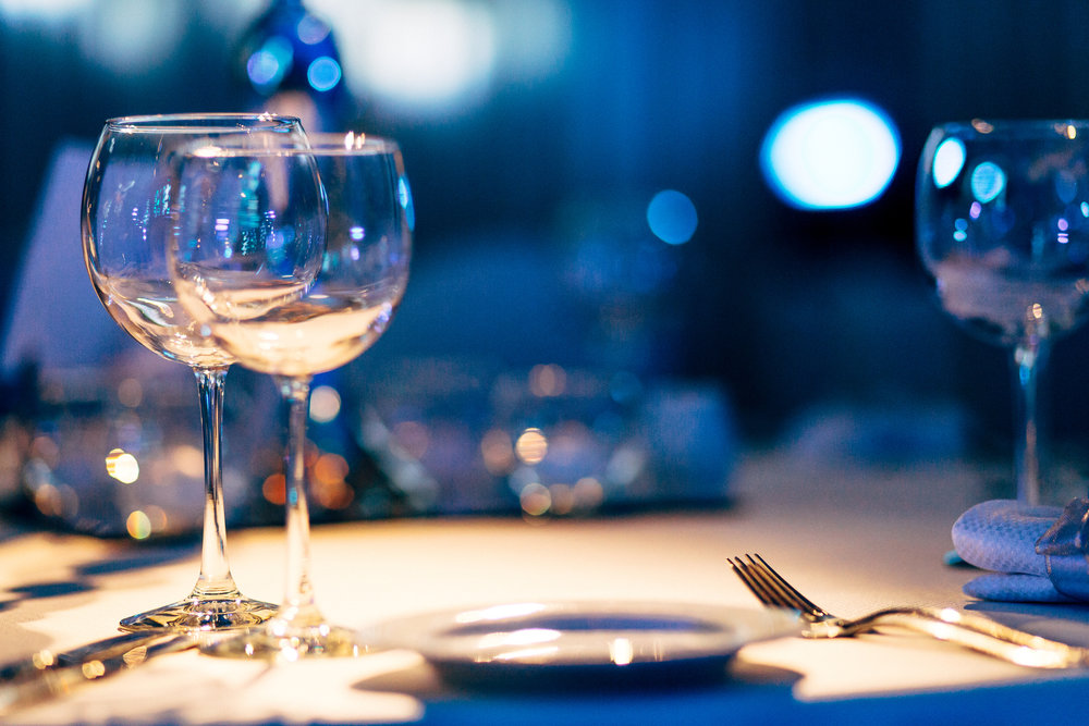 A pair of wine glasses sit atop a white tablecloth at an elegant restaurant.