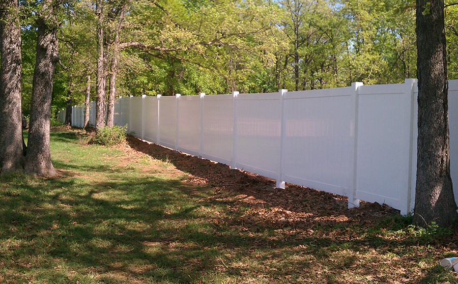 vinyl fence in a backyard with trees