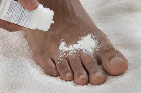 34447879_S_african_american_foot_odor_powder_toes_hand.jpg