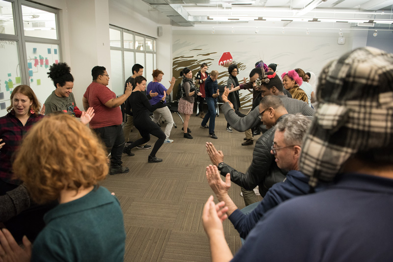 The audience at Theater of the Oppressed warms up together at a scene sharing workshop. Photo by Alex Woodhouse.