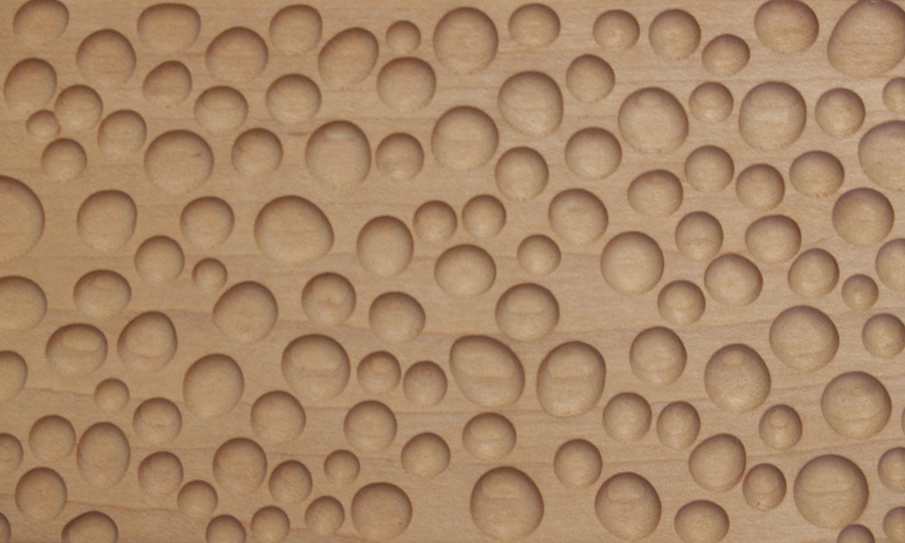 Circle texture   This texture was inspired by raindrops on a piece of glass. We used a ball endmill to create a rounded effect for each circular pocket. Here it is shown in natural maple. This whimsical texture is great for mirror frames and other decorative panels.