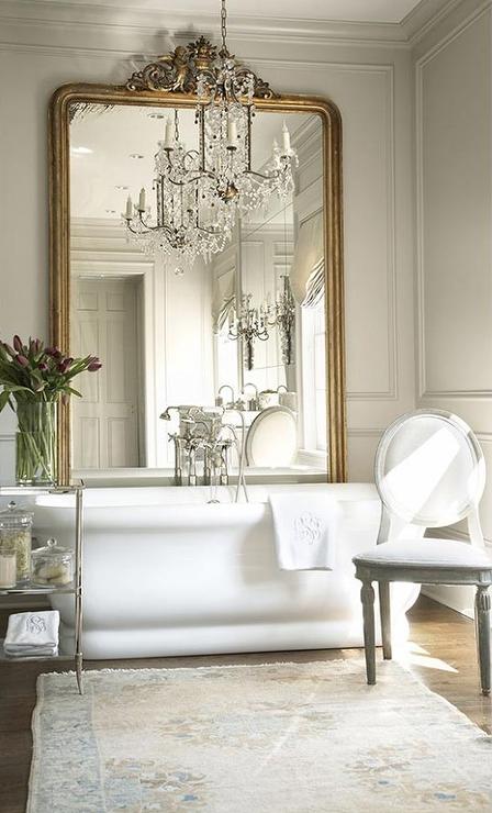 gilt-floor-mirror-behind-tub-chandelier-above-bathtub-elegant-master-bath.png