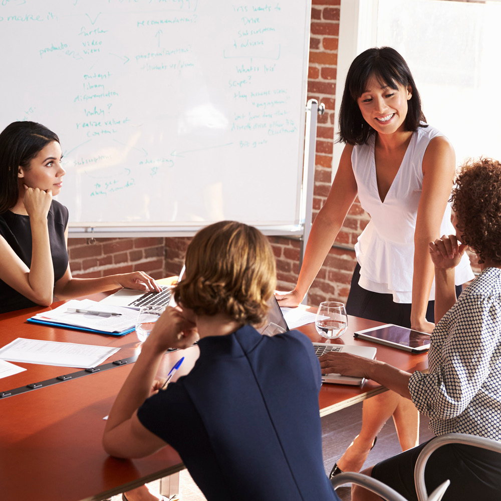Artsmarketing Services provides training and strategy to help your inhouse campaign and campaign manager get elevated results. Image of men and women talking around a conference table.