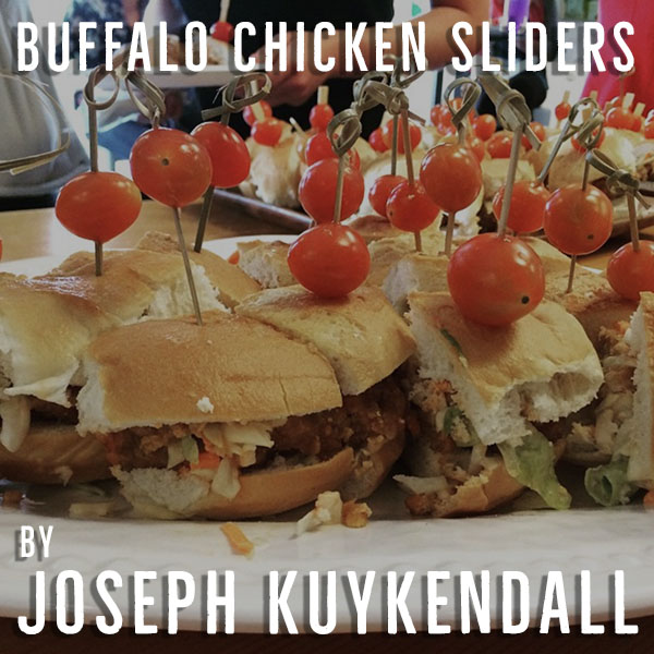 """A simple way to enjoy the great flavors of buffalo chicken at a tailgate. Ground chicken together with many spices and buffalo flavored pretzels on a soft bun topped topped with a (football) tomato make for a simple yet succulent tailgate option. Can be done with many variations including gluten free pretzels and bread to please all types of diets!"""