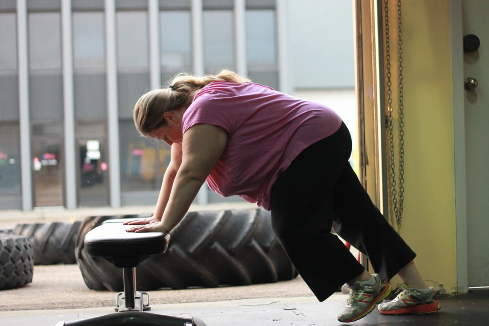 Sky performs a modified burpee using a bench and walk-out technique.