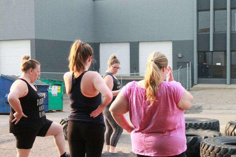 """CPT Marsha leads a group through """"Tire Flipping"""" and """"Sledging"""" as part of a program on Functional Fitness"""
