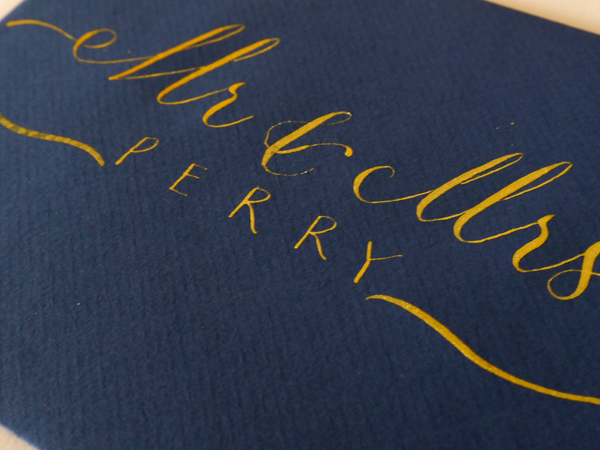 Modern calligraphy wedding envelopes in gold ink