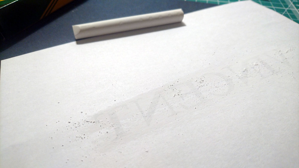 Chalk applied to the back of paper in order to trace lettering onto dark card stock