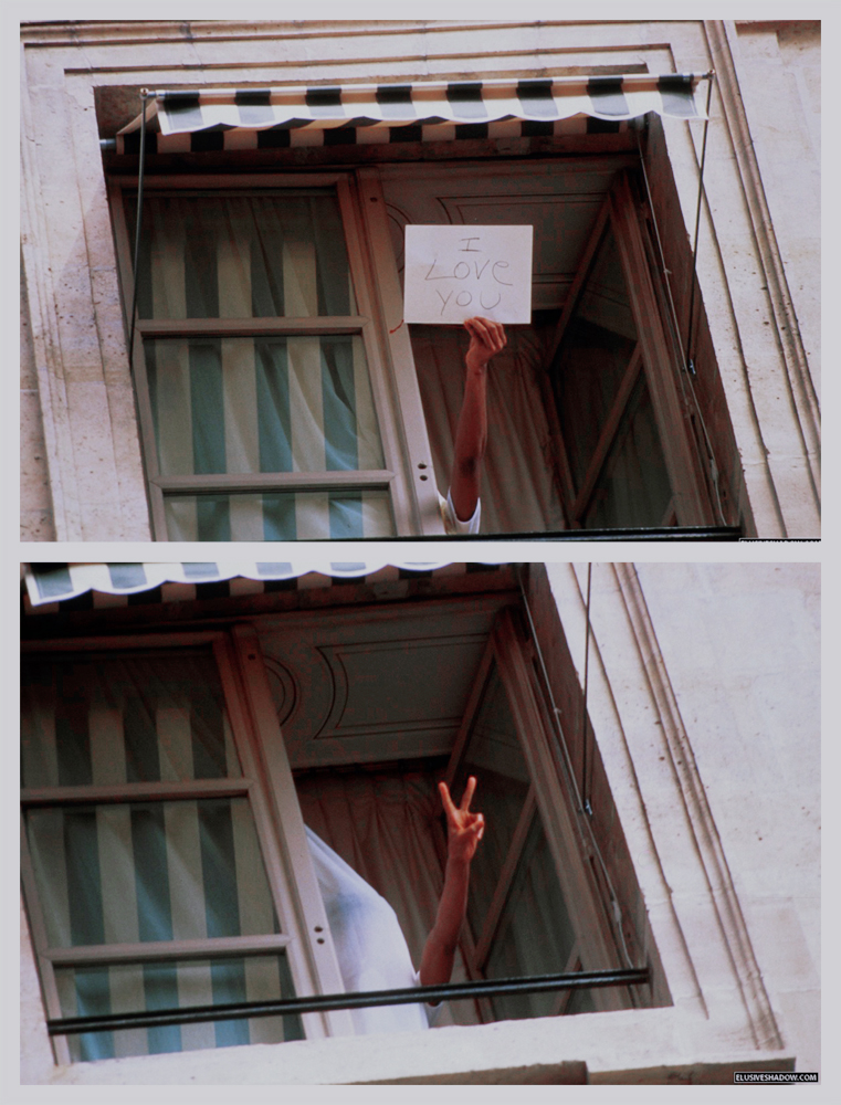 Michael Jackson holding up a sign at a hotel window