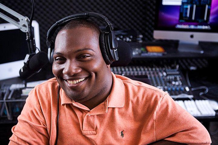 Alex wearing headphones in a studio, smiling.