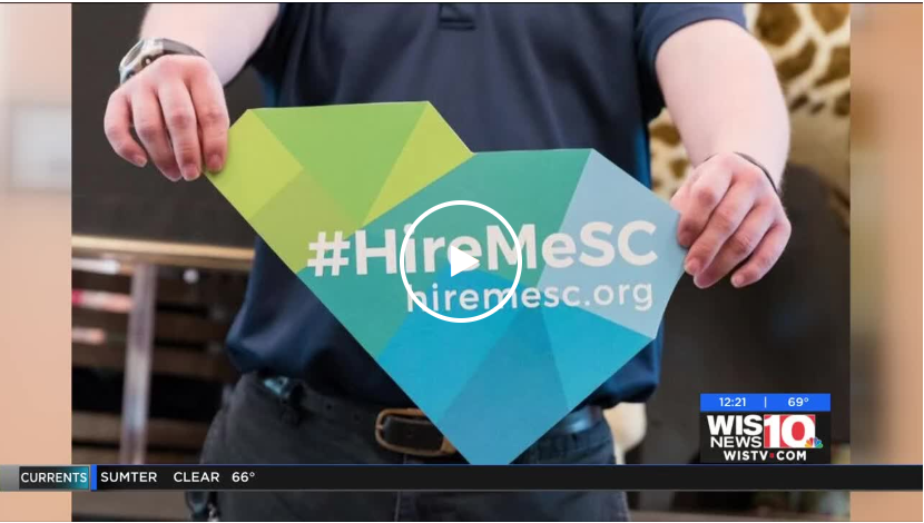 Screenshot of the WIS News 10 video. A young man holding the #HireMeSC sign at waist height.
