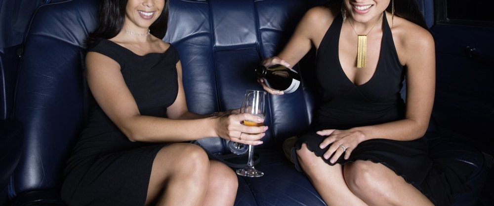 Portrait of two women drinking champagne in back seat of car