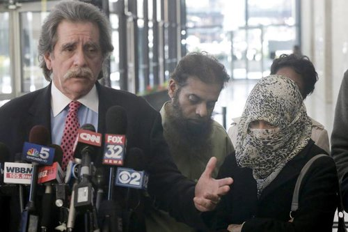 Attorney Thomas Durkin, left, talks to reporters as Mohammed Hamzah Khan's parents stand nearby, after a court hearing in October 2014 in Chicago. PHOTO: CHARLES REX ARBOGAST/ASSOCIATED PRESS