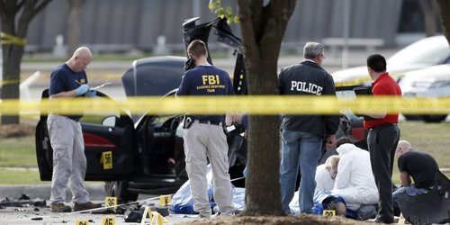 FBI crime scene investigators document the area around two deceased gunmen and their vehicle outside the Curtis Culwell Center in Garland, Texas, in May 2014.