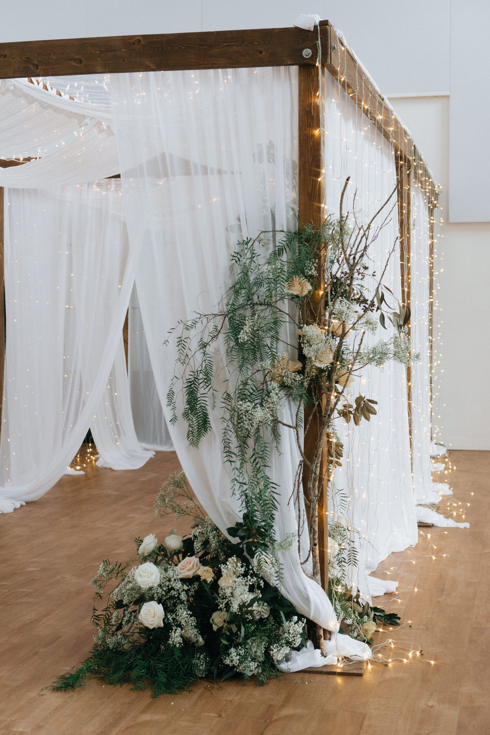 The gals transformed the entrance from our foyer into the main space with a canopy of twinkle lights and floral arrangements to die for.