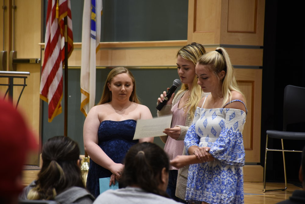 Kayla, Alison and Erin, students from Quincy High School, reading impact statements about the personal effects of the opioid crisis on each of their families.
