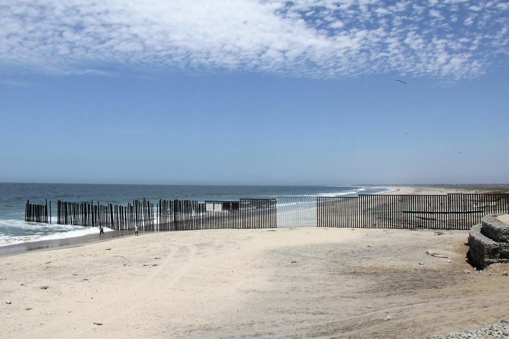 "Part of the border fence that separates the United States from Mexico, where artist Ana Teresa Fernández has painted a section to match the sky to ""erase"" the fence. All photos courtesy of the artists"