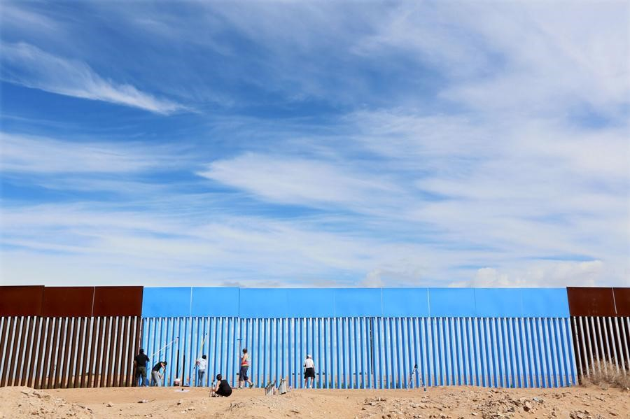 Volunteers paint the border fence between the United States and Mexico to give the illusion of transparency during the Borrando la Frontera, or Erasing the Border, art project in Mexicali, Mexico, on April 9, 2016.  Sandy Huffaker / Reuters