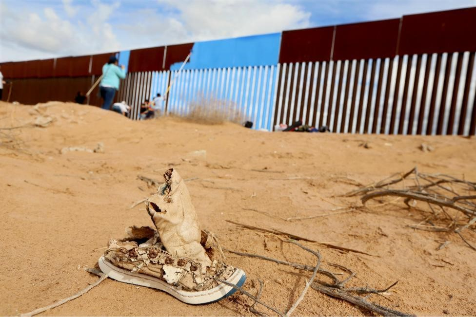 Volunteers paint the border fence in Mexicali, Mexico. REUTERS/Sandy Huffaker