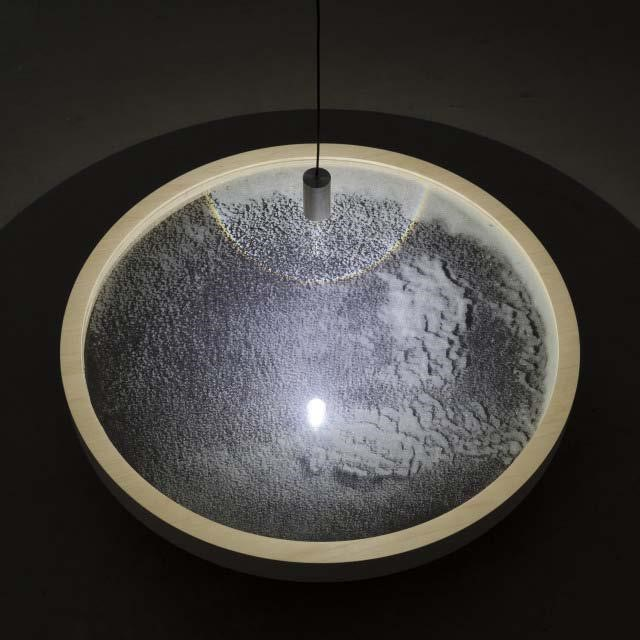 "Chris Fraser, ""SCRY"" (2013), Glass Microspheres, Plate Glass, Maple Plywood, LED Pendant,    25 3/4″ Diameter x 6″"