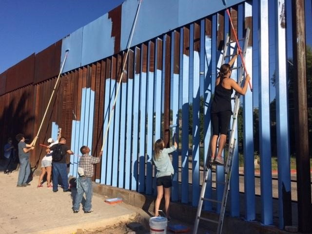 """NOGALES, Mexico - Armed with sky-blue paint, artist Ana Teresa Fernandez began to """"erase"""" the border fence that splits up Mexico and the U.S. on Tuesday."""