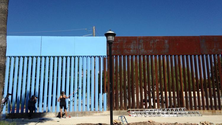 "Artist Ana Teresa Fernandez paints the U.S.-Mexico border wall blue to ""lower the sky"" as part of the art installation, ""Borrando la Frontera,"" or ""Erasing the Border,"" in Nogales, Mexico, last week. (Valeria Fernandez / Associated Press)"