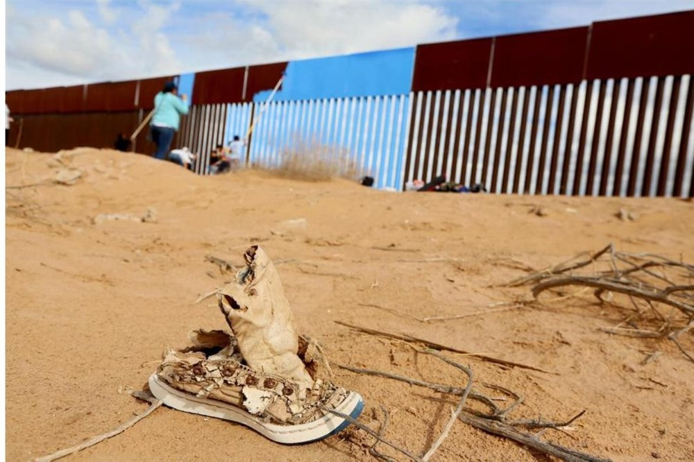 Volunteers paint the border fence between the United States and Mexico in Mexicali, Mexico, on April 9, 2016.  #   Sandy Huffaker / Reuters