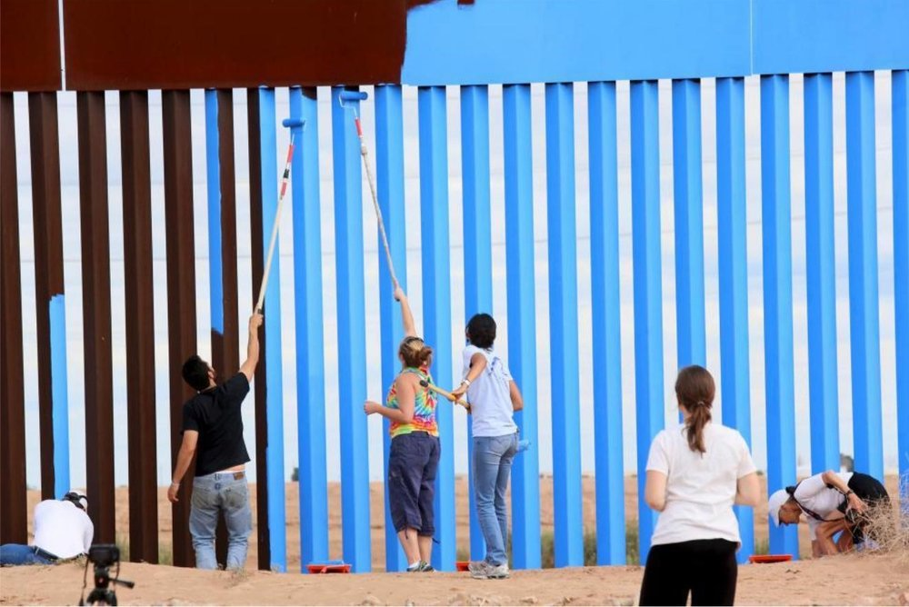 Volunteers paint the border fence between the United States and Mexico to give it the illusion of transparency. REUTERS/Sandy Huffaker