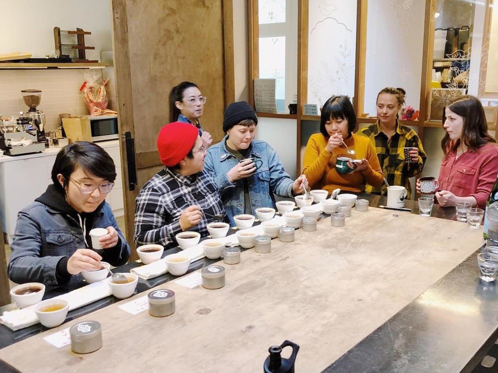 A production cupping at Andytown Coffee with Corey Turner (black beanie) and Corazon Padilla (gold shirt).