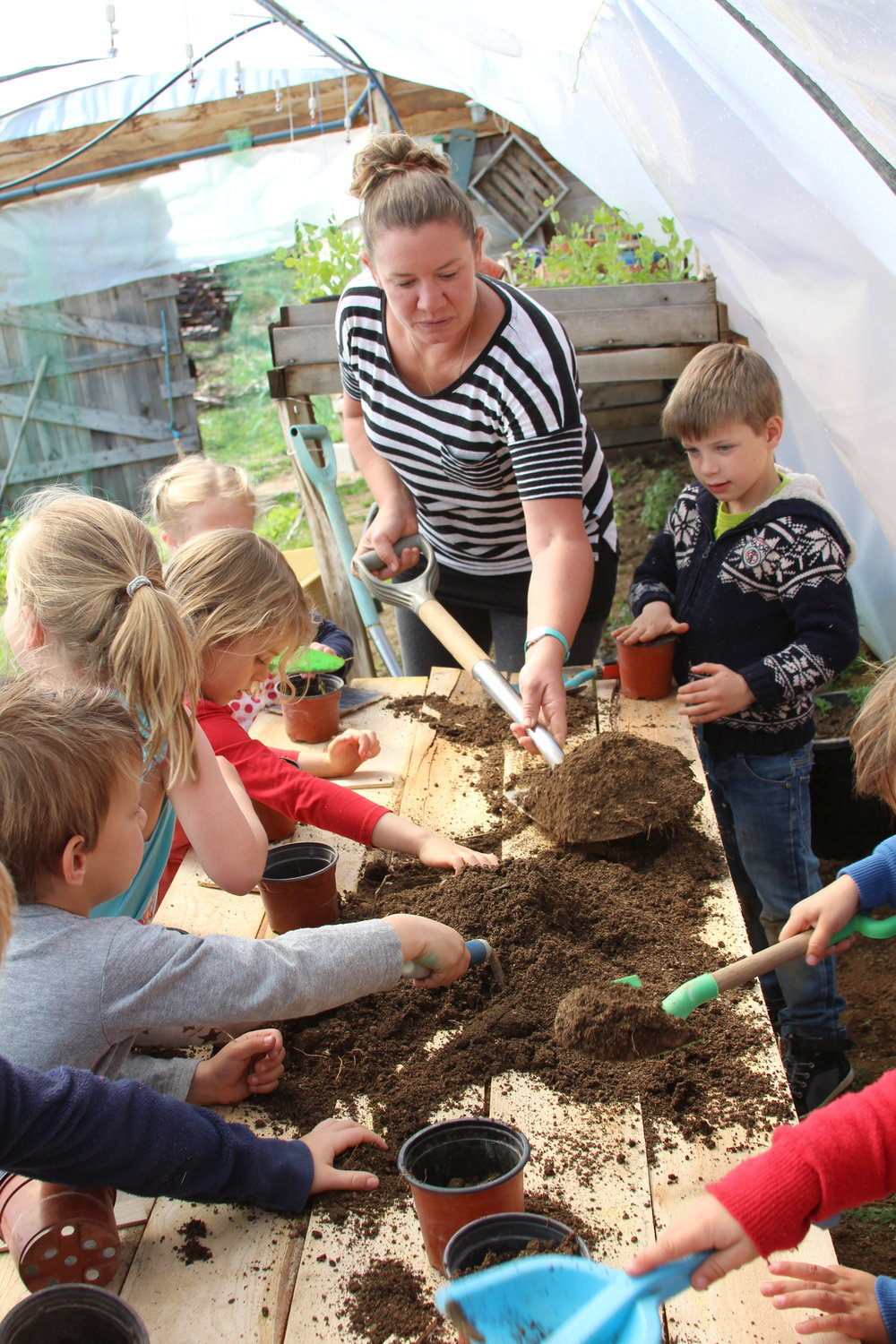Dani, giving children a lesson in planting pumpkin seedlings