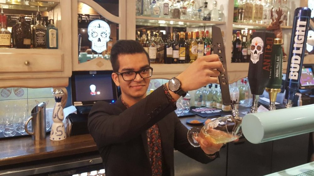 Restaurant manager Abhi pouring up an ice-cold cider.
