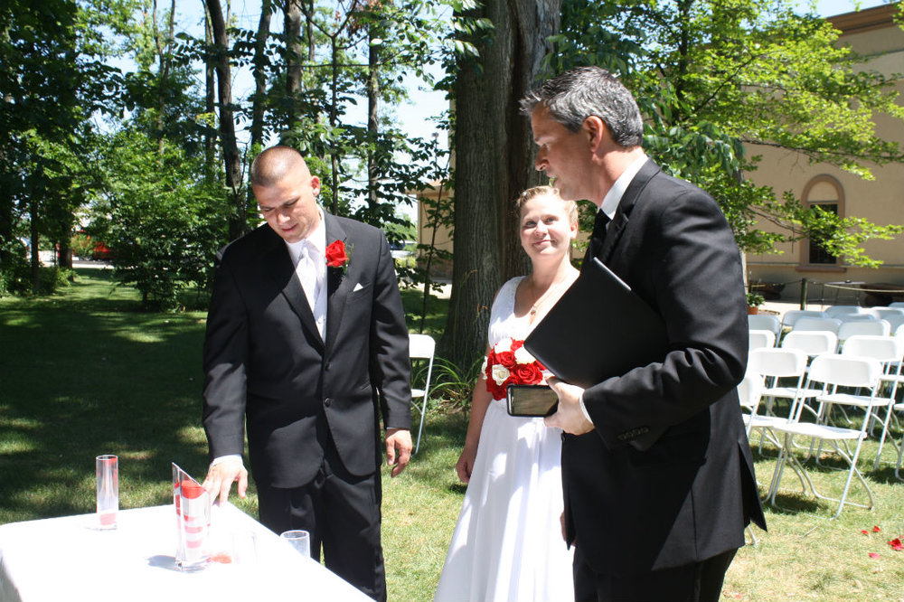 Ohio wedding officiant, Damian King, of Columbus talks to bride and groom, Danielle and Bill about their sand ceremony