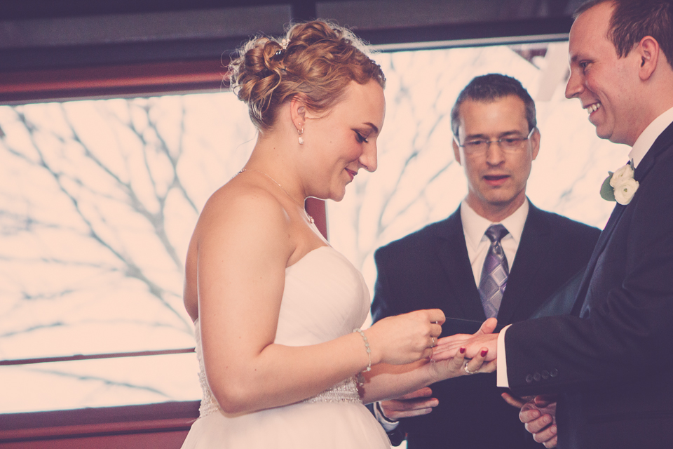 bride places wedding ring on groom's hand as officiant looks on in Columbus