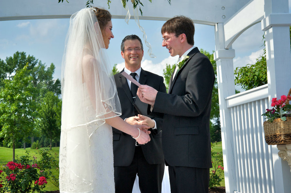 Officiant Damian King hears personal vows read by Justin at wedding in Columbus Ohio