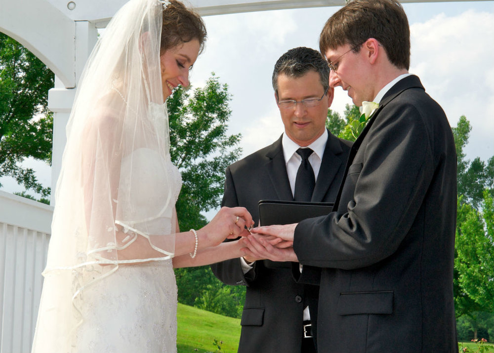 Columbus, Ohio wedding. Officiant Damian King looks on as Alison places ring on Justin's finger