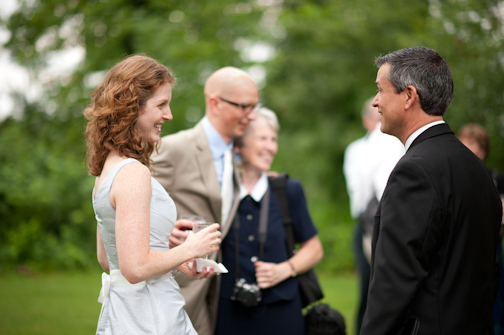 Bride chats with her wedding officiant near Columbus Ohio. Groom in background